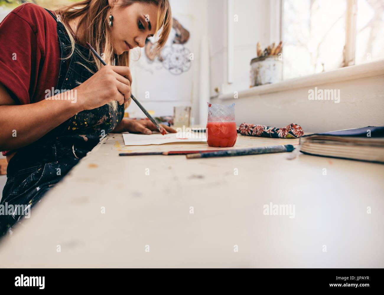 Immagine di donna bellissima foto di disegno nella sua officina. Artista femminile dipinto nel suo studio. Immagini Stock