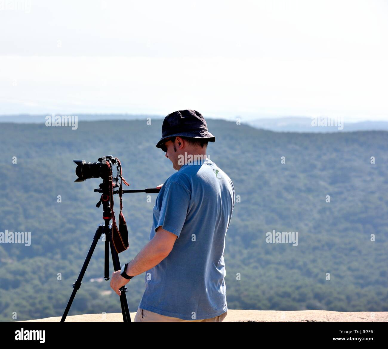 Uomo che utilizza SLR Fotocamera digitale su un treppiede Immagini Stock