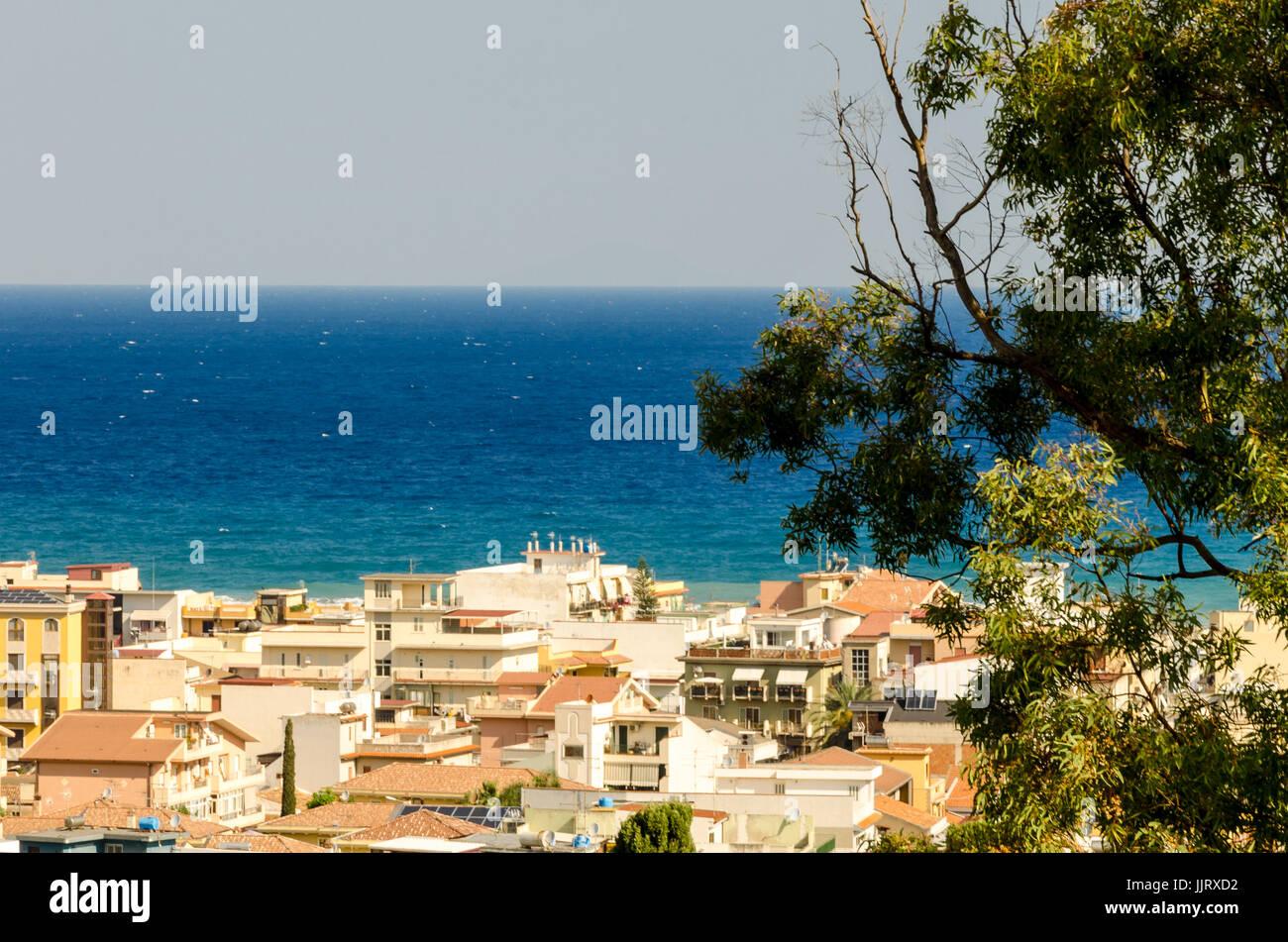 In intensità di colore blu del Mare Mediterraneo, si affacciano le case di un paese siciliano Immagini Stock