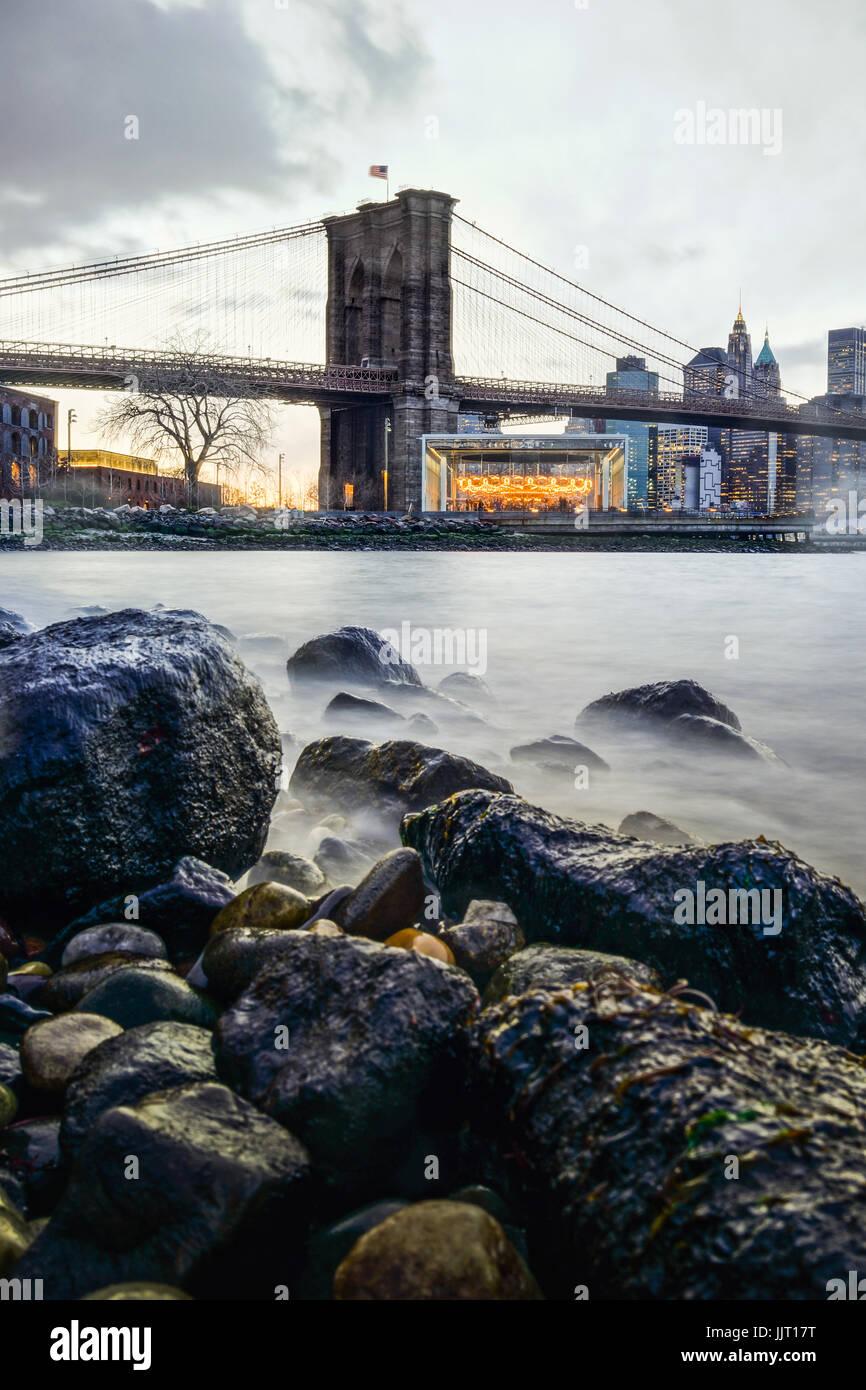 Manhattan Bridge e NYC skyline notturno con la riflessione della skyline su East River Immagini Stock