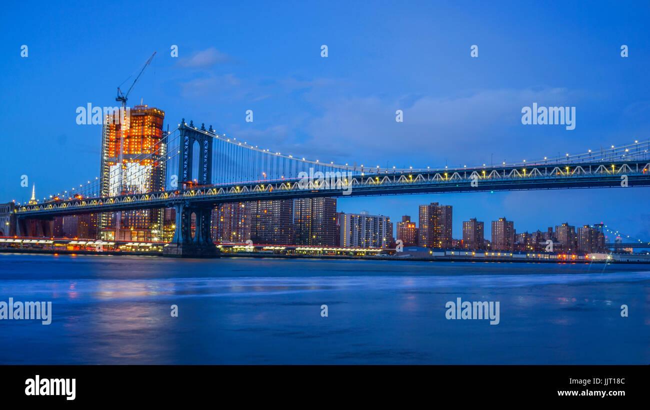 Il Ponte di Brooklyn e NYC Skylinet notte con la riflessione della skyline su East River Immagini Stock