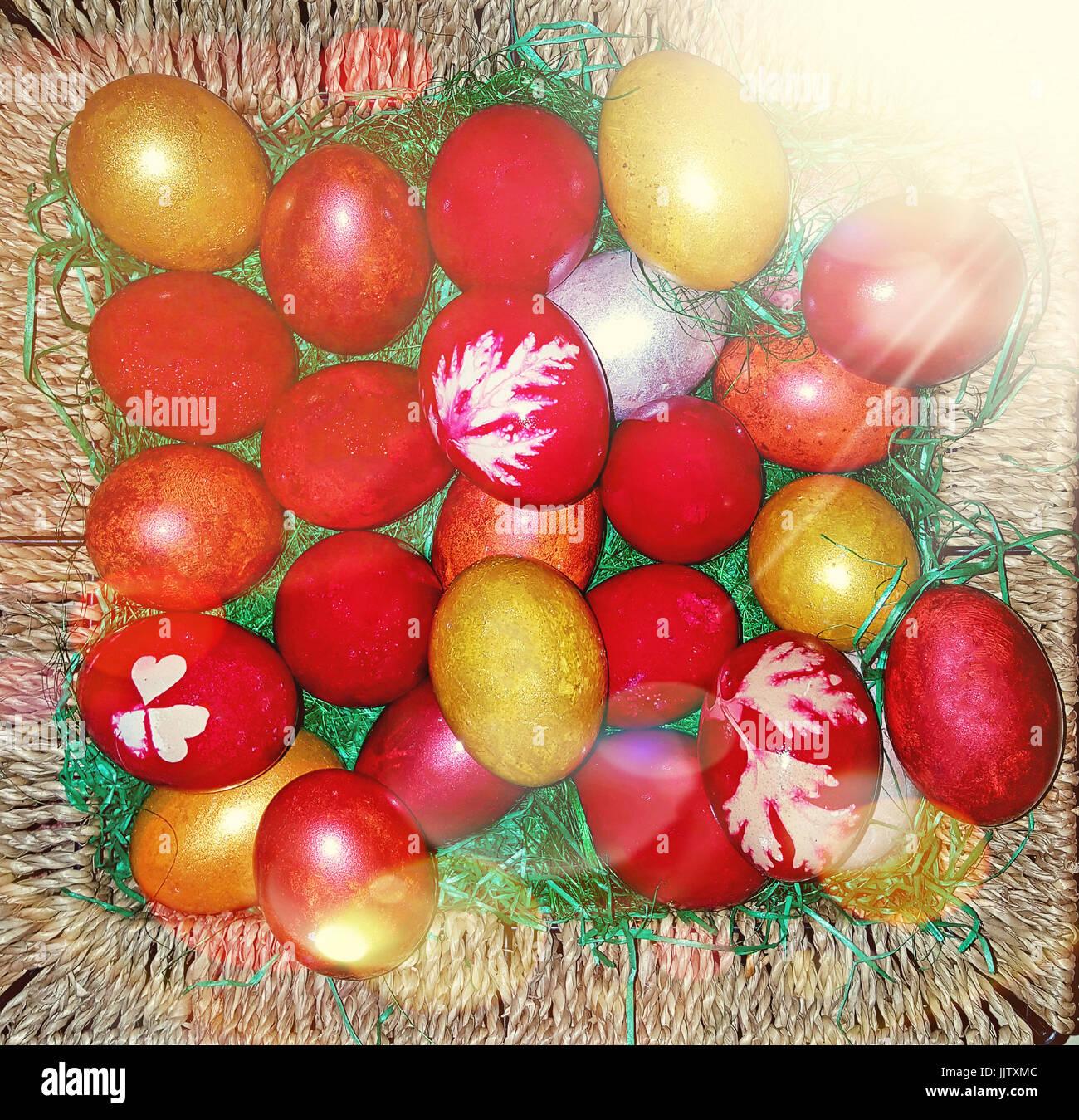 Colorati dipinti tradizionali uova di pasqua in un cestello di marrone con raggi divina luci. Immagini Stock