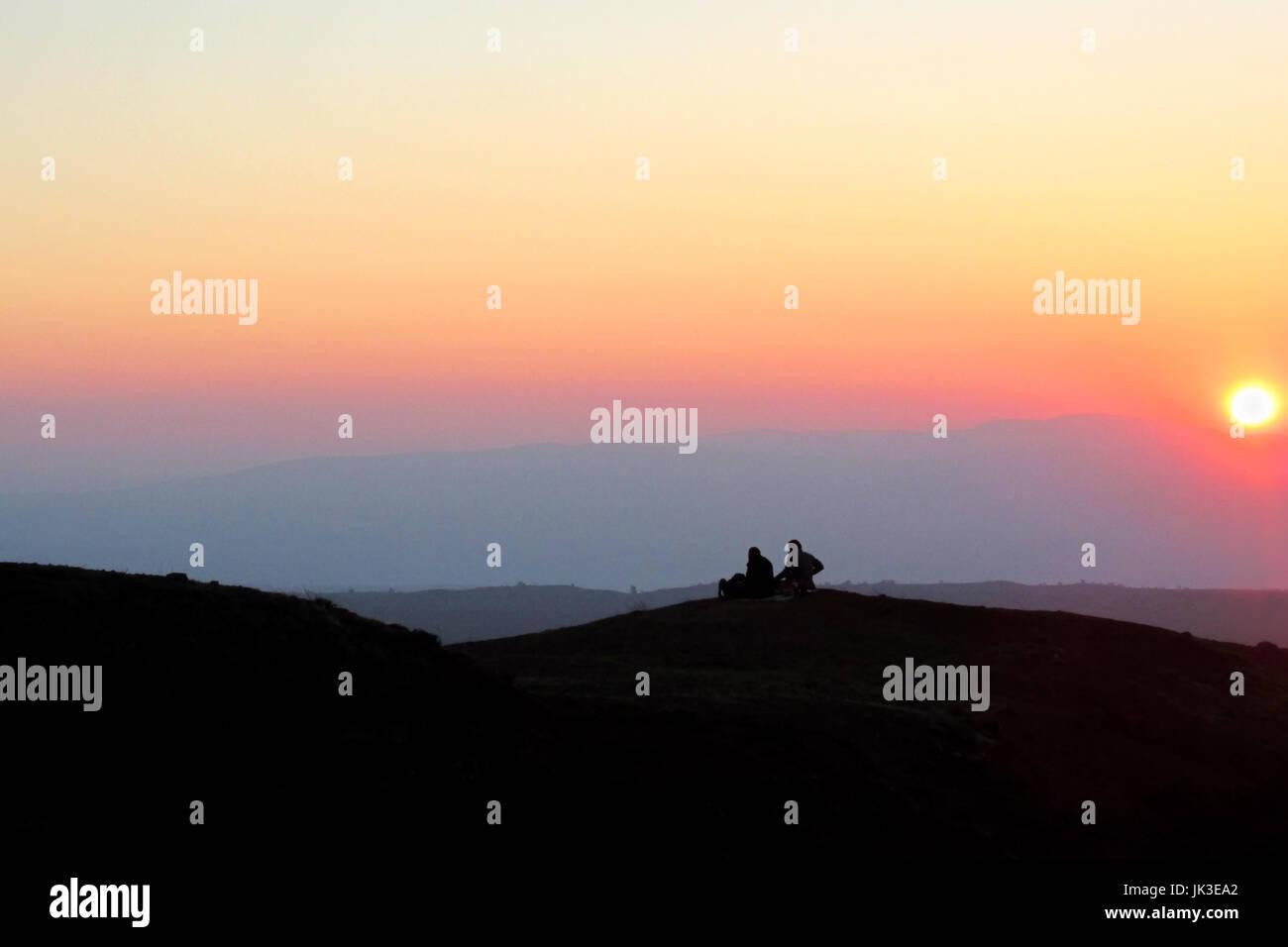 Un paio di sedersi su una collina stagliano dal sole al tramonto vicino al Monte Bental in Israele il Golan. Foto Stock