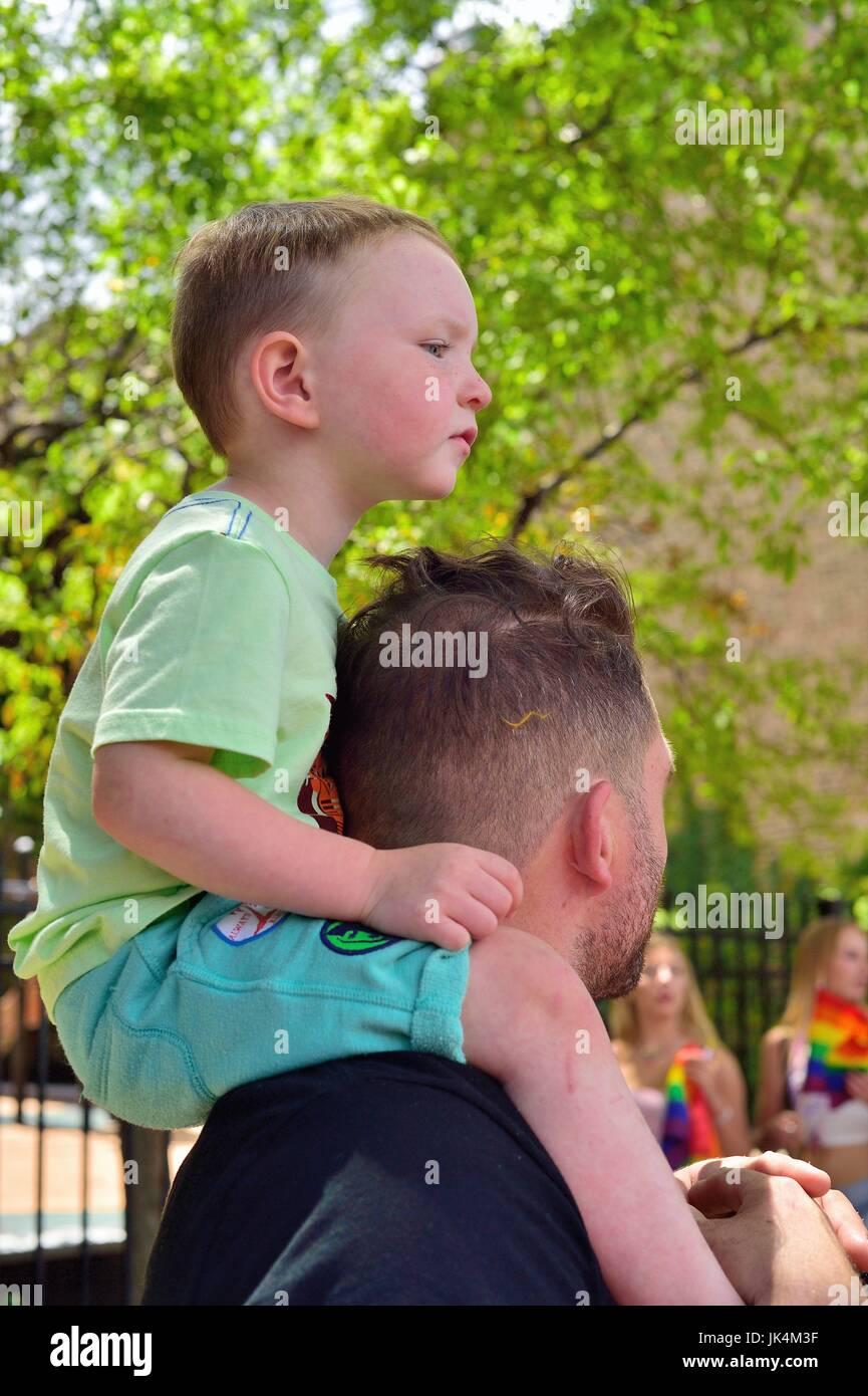 Giovane ragazzo per ottenere una vista in elevazione del Chicago il Gay Pride Parade. Il corteo viene tenuto ogni Immagini Stock