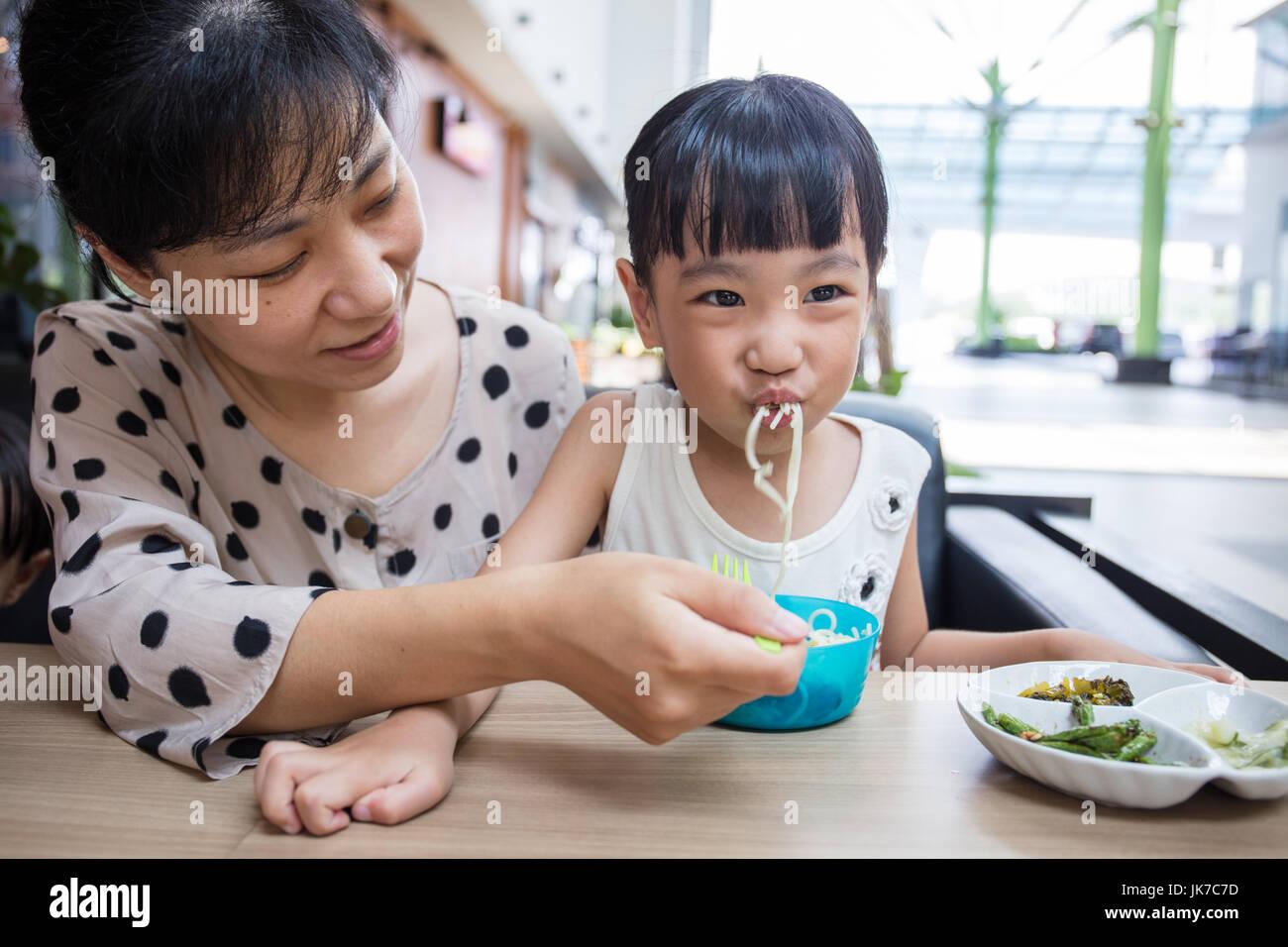 Asian madre cinese e la figlia di mangiare carne di manzo tagliatelle in outdoor cafe Immagini Stock