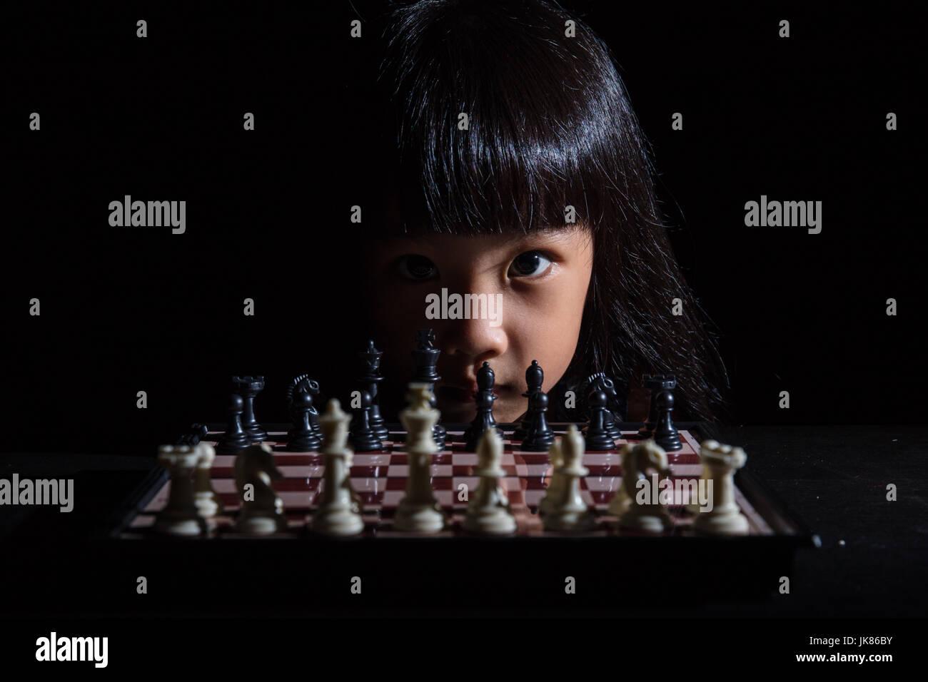 Asian poco ragazza cinese di giocare a scacchi in isolati su sfondo nero Immagini Stock