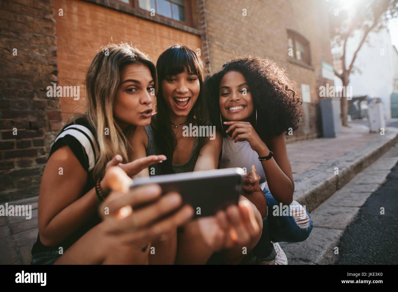 Amici di sesso femminile seduti all'aperto e rendendo selfie con smart phone. Multi gruppo etnico di donne appendere Immagini Stock