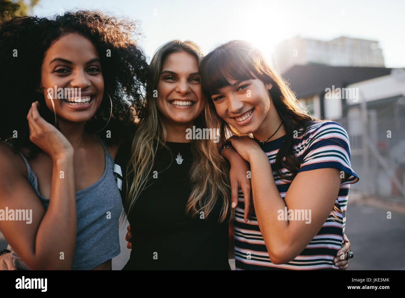 Colpo all'aperto di tre giovani donne divertimento sulla strada della citta'. Multirazziale amiche godendo Immagini Stock