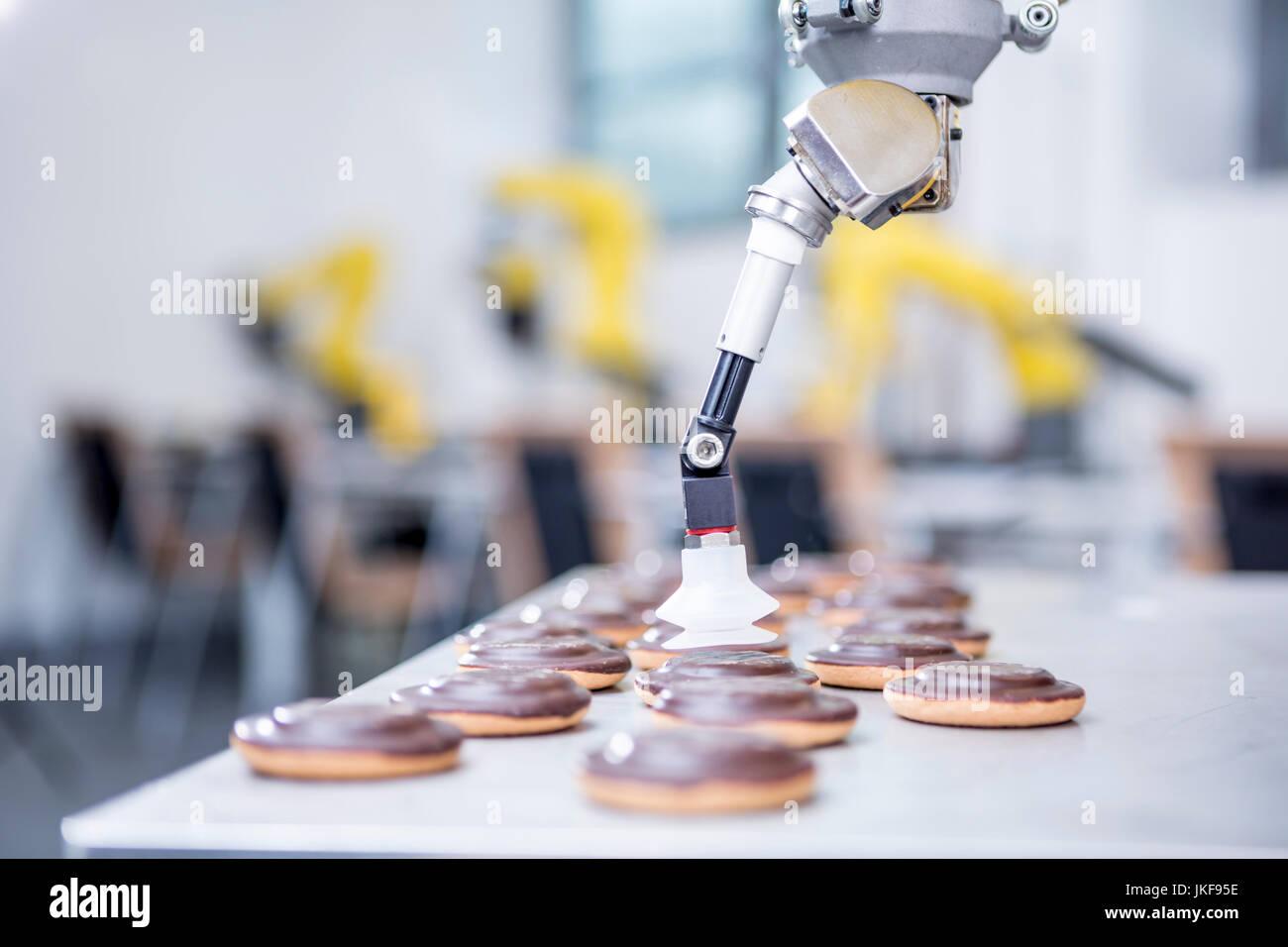 Close-up di robot industriali di manipolazione dei cookie Immagini Stock