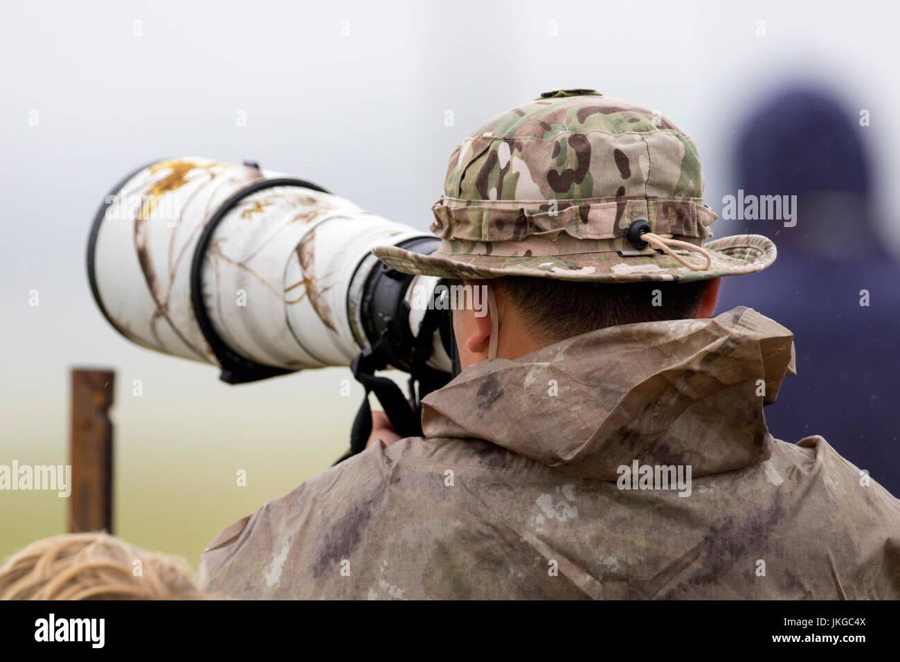 Fotografo professionista che indossa il camuffamento riprese con una fotocamera Canon e EF500mm f4 super teleobiettivo Immagini Stock