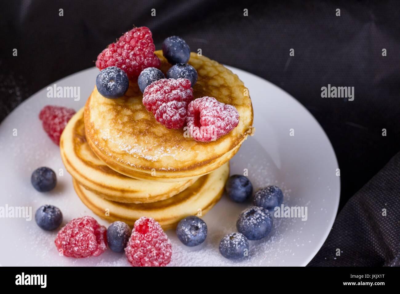 Pila di pancake con lamponi e mirtilli rivestite con zucchero a velo sulla piastra bianca e sfondo nero Immagini Stock