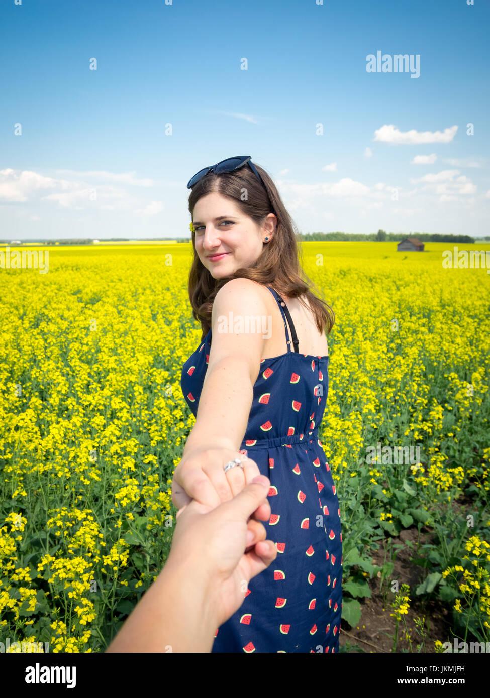 Da un follow me di punto di vista, un giovane uomo è portato in un campo di canola con la sua giovane moglie. Immagini Stock