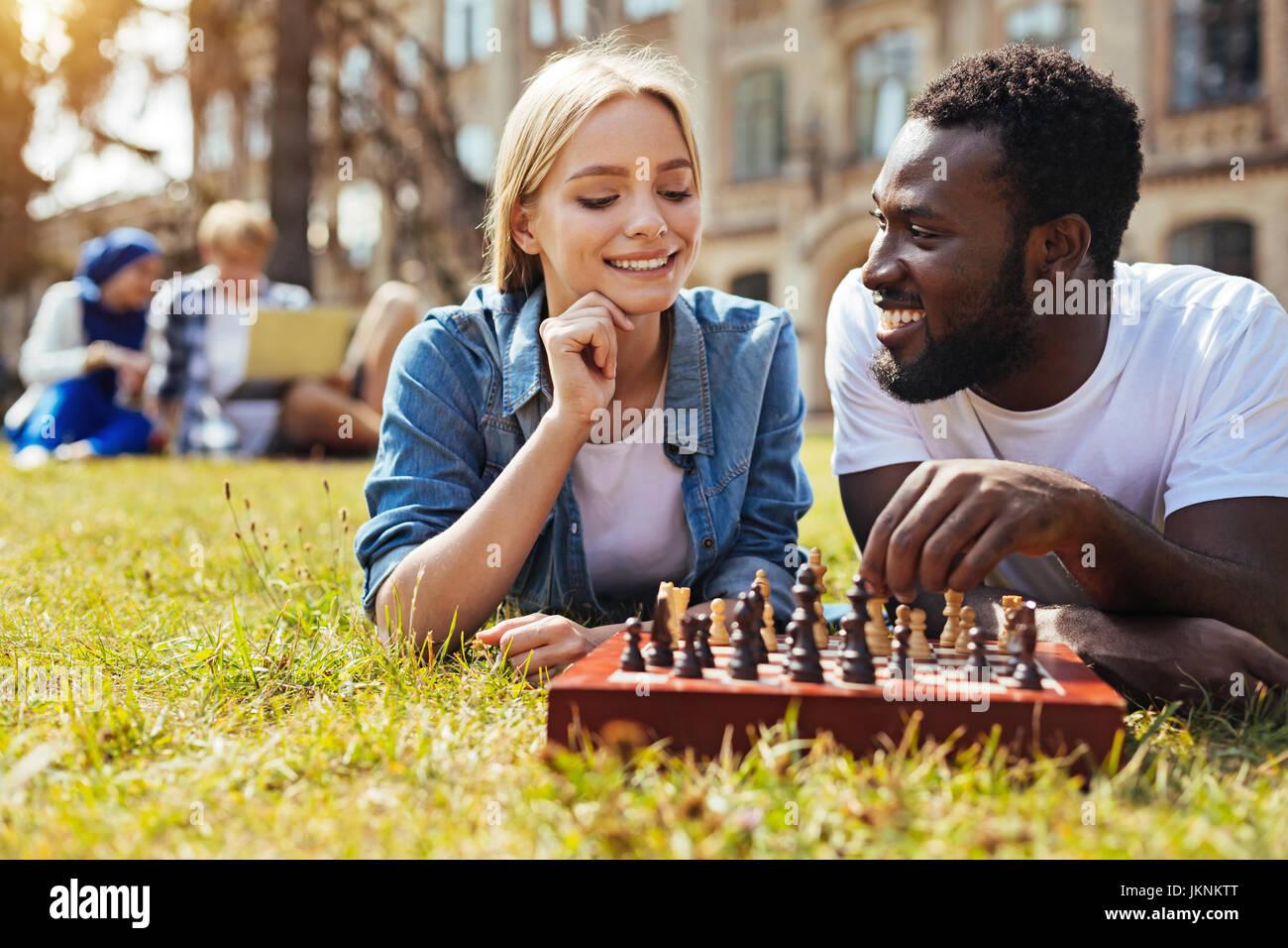 Positivo pretty woman insegnando il suo amico giocare a scacchi Immagini Stock