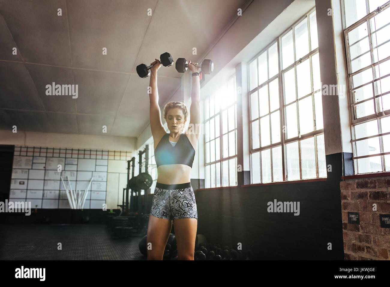 Atleta excercising con manubri per il muscolo e forza edificio. Giovane donna il sollevamento pesi in palestra . Immagini Stock