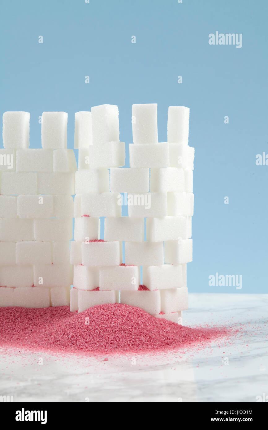 Un castello costruito con zolletta di zucchero e sabbia rosa ai suoi piedi. Minimal design innovativo e divertente Immagini Stock