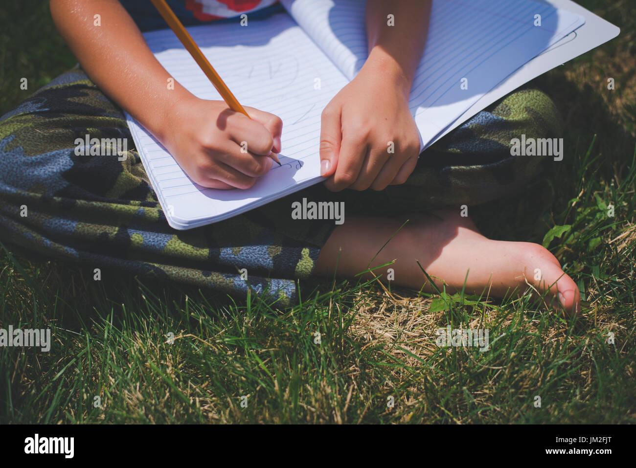 Una gioventù scrive in un notebook per l'istruzione scolastica apprendimento a scuola. Immagini Stock
