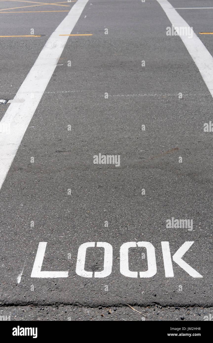 Guardare segno dipinto su un crosswalk pedonale Immagini Stock
