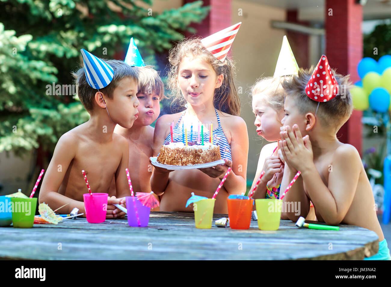 Compleanno con i bambini in cappelli in estate. Immagini Stock