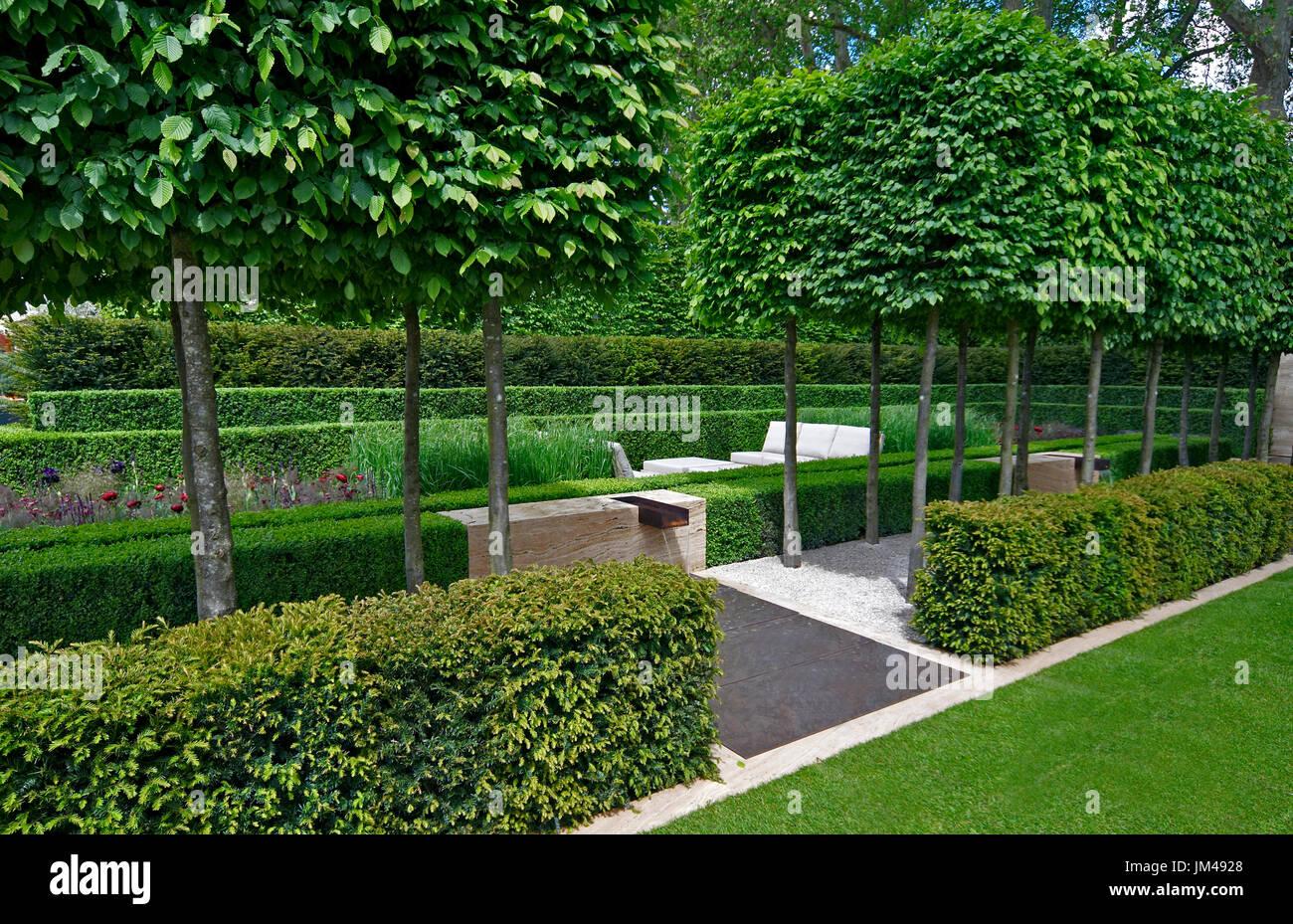 Un classico giardino con un viale di yew, box e carpino portando ad una funzione di acqua e la scultura Immagini Stock