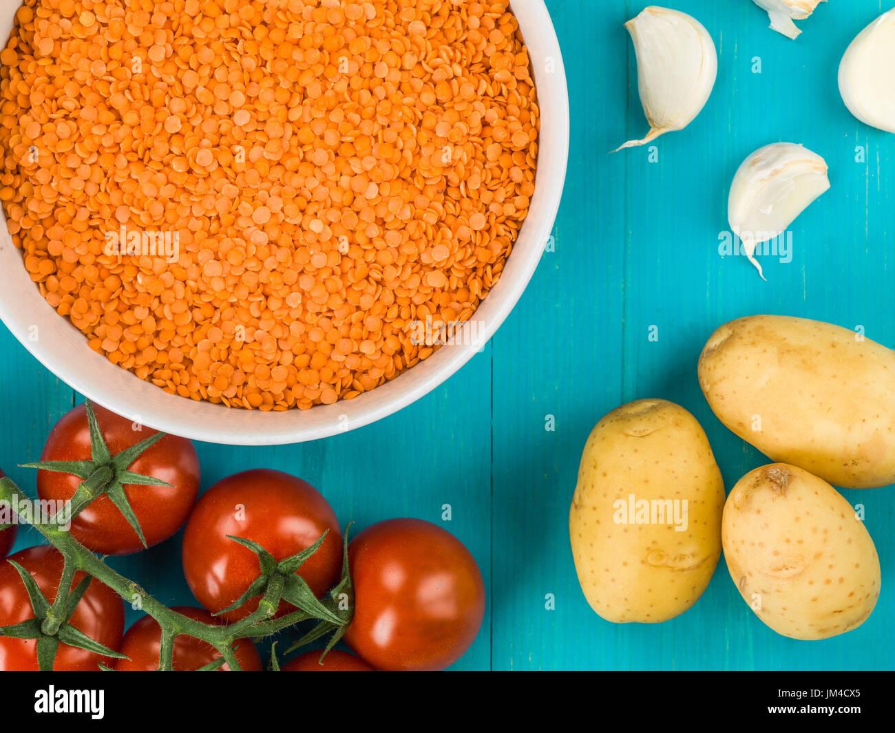 Ciotola di cotte a secco di lenticchie rosse contro un blu sullo sfondo di legno Immagini Stock