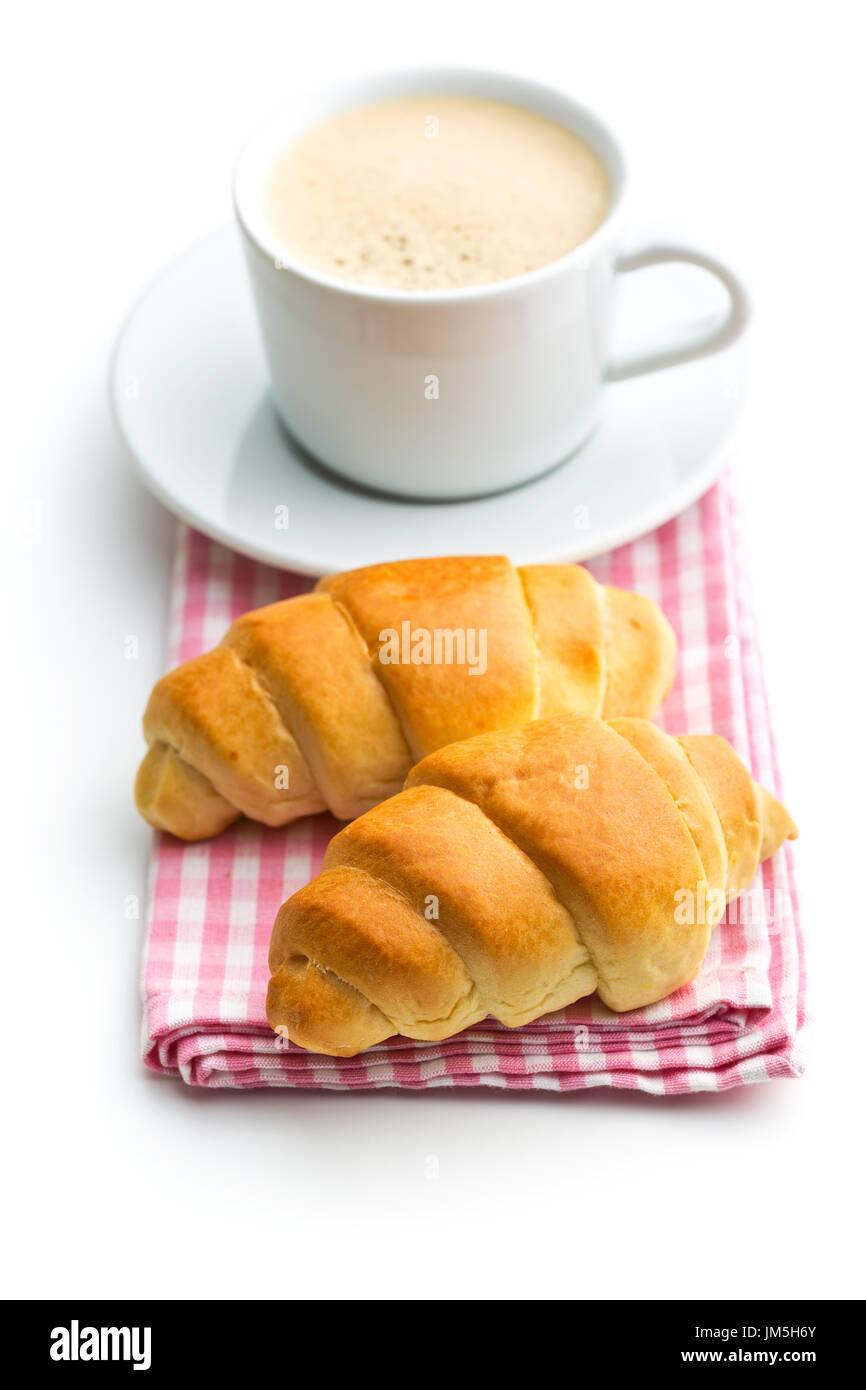 Gustosi croissant burroso e tazza di caffè isolato su sfondo bianco. Immagini Stock