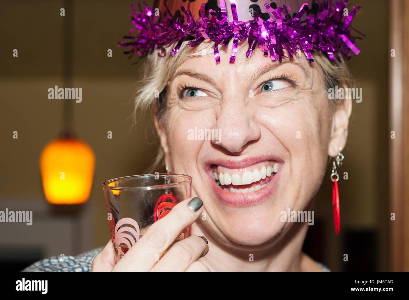 Una donna che indossa un cappello di partito ad una festa di compleanno. Immagini Stock