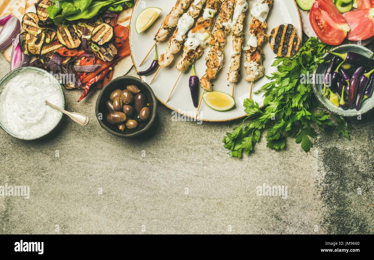 Flatlay di grigliate di spiedini di pollo, focacce, prezzemolo, ortaggi, olive Immagini Stock