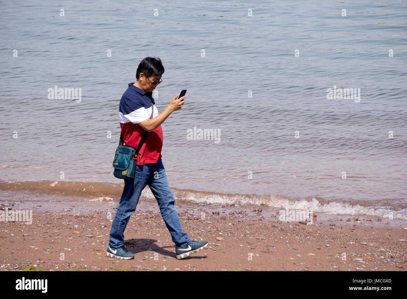 Uomo a camminare lungo la spiaggia guardando il suo telefono Immagini Stock
