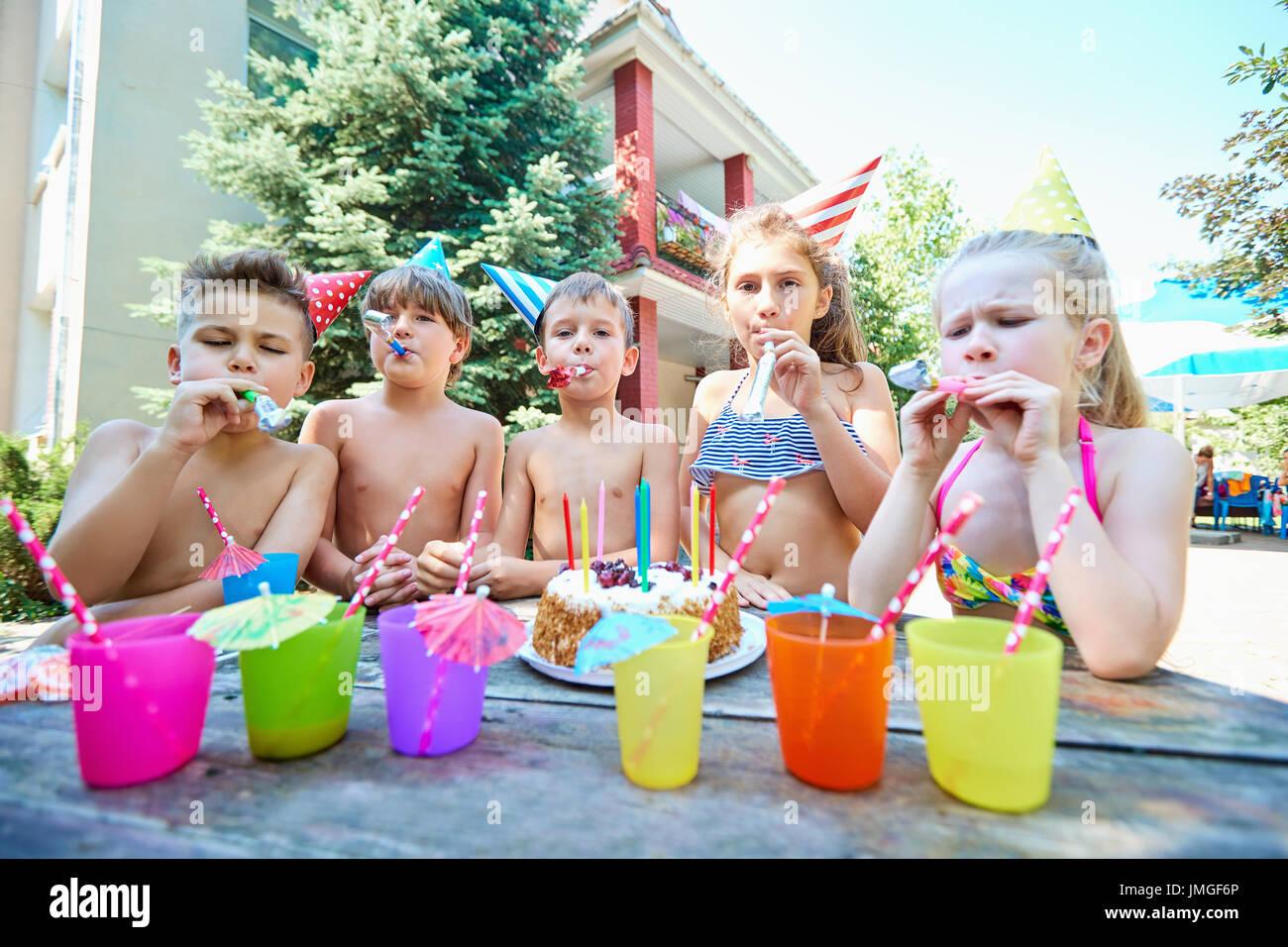 Compleanno con i bambini in cappelli in estate Immagini Stock