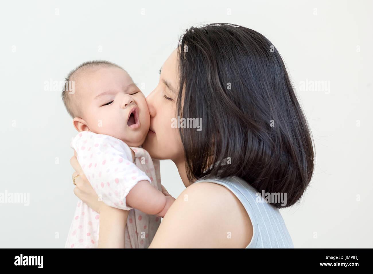 Ritratto di felice madre asiatica baciando e abbracciando il suo grazioso piccolo bambino su sfondo grigio Foto Stock