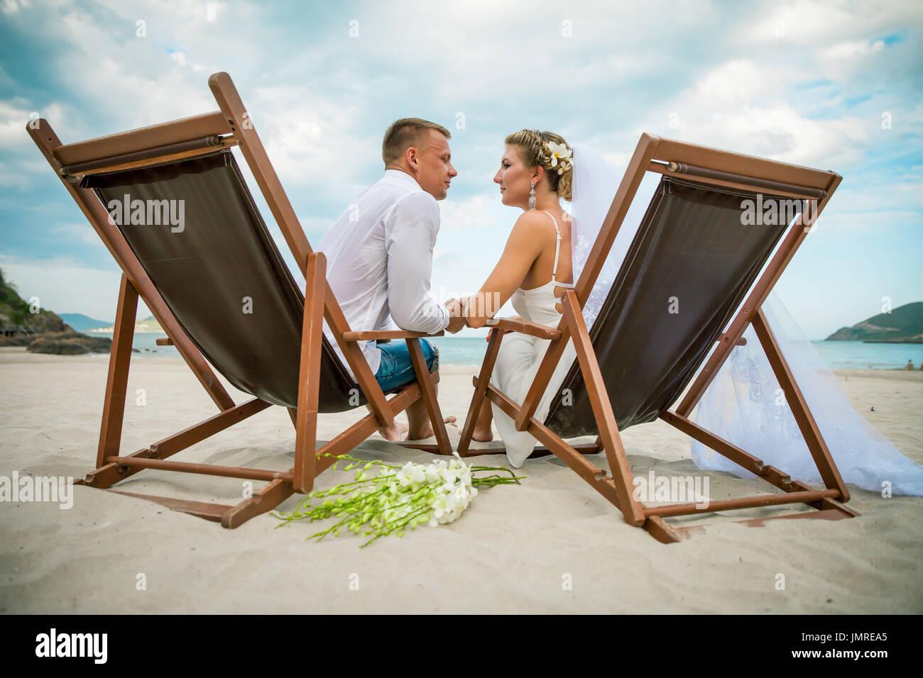 Lo Sdraio O La Sdraio.Sposa E Lo Sposo Seduto Nella Sedia A Sdraio In Riva Al Mare Il