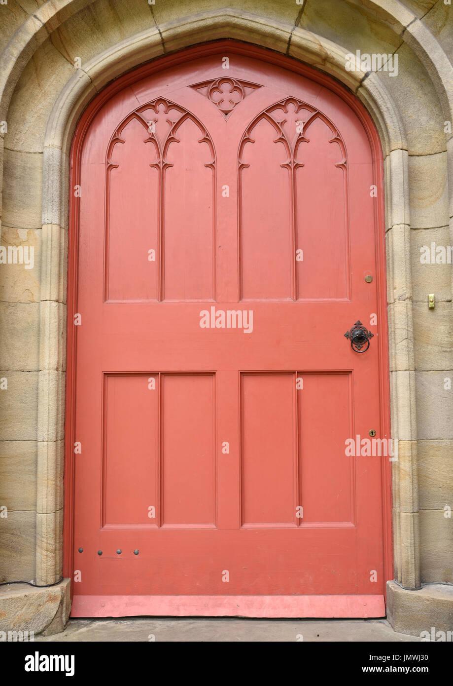 In legno rosso porta della chiesa in pietra circondano Chiesa di tutti i santi di stand Immagini Stock