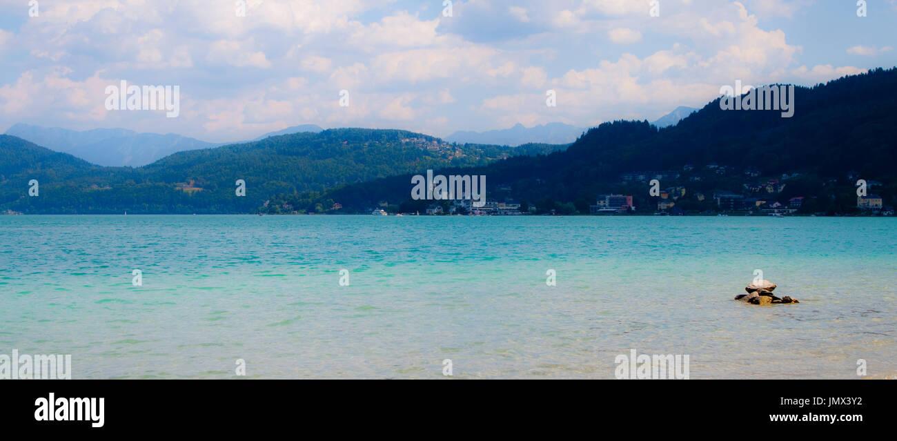 Un suggestivo paesaggio presso il lago Wörthersee, Austria - montagne bluastro stanno sprofondando in turquise acqua blu Immagini Stock