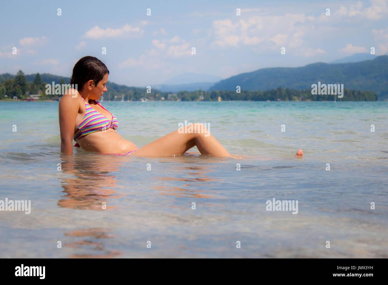 Una donna godendo una giornata di sole al Wörthersee in Austria Immagini Stock