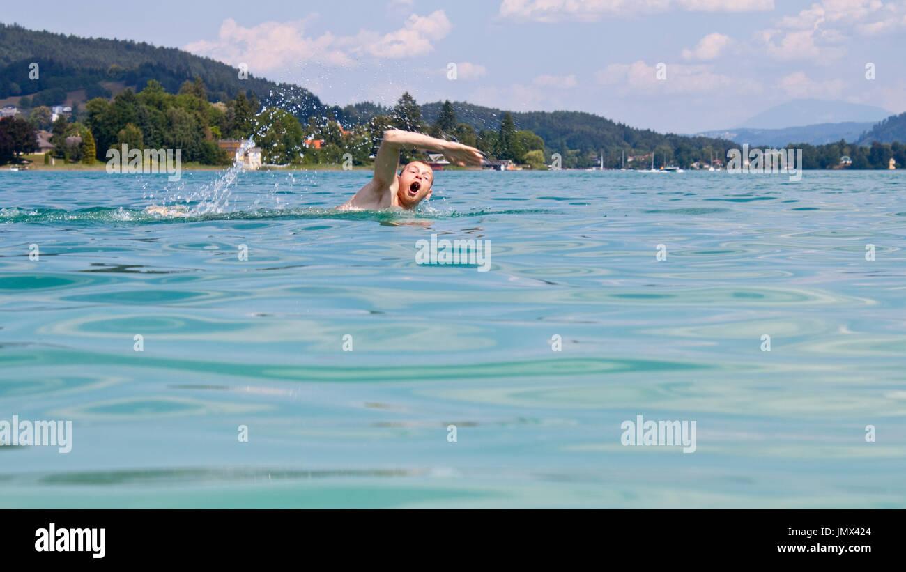 Un uomo di nuoto nel lago Wörthersee, Austria Immagini Stock