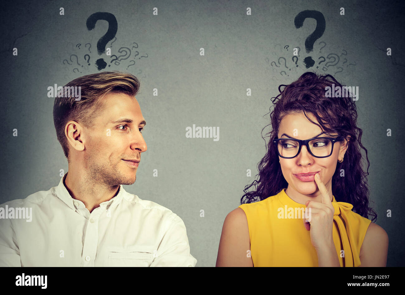 Uomo e donna con punto interrogativo guardando ogni altra con interesse Immagini Stock