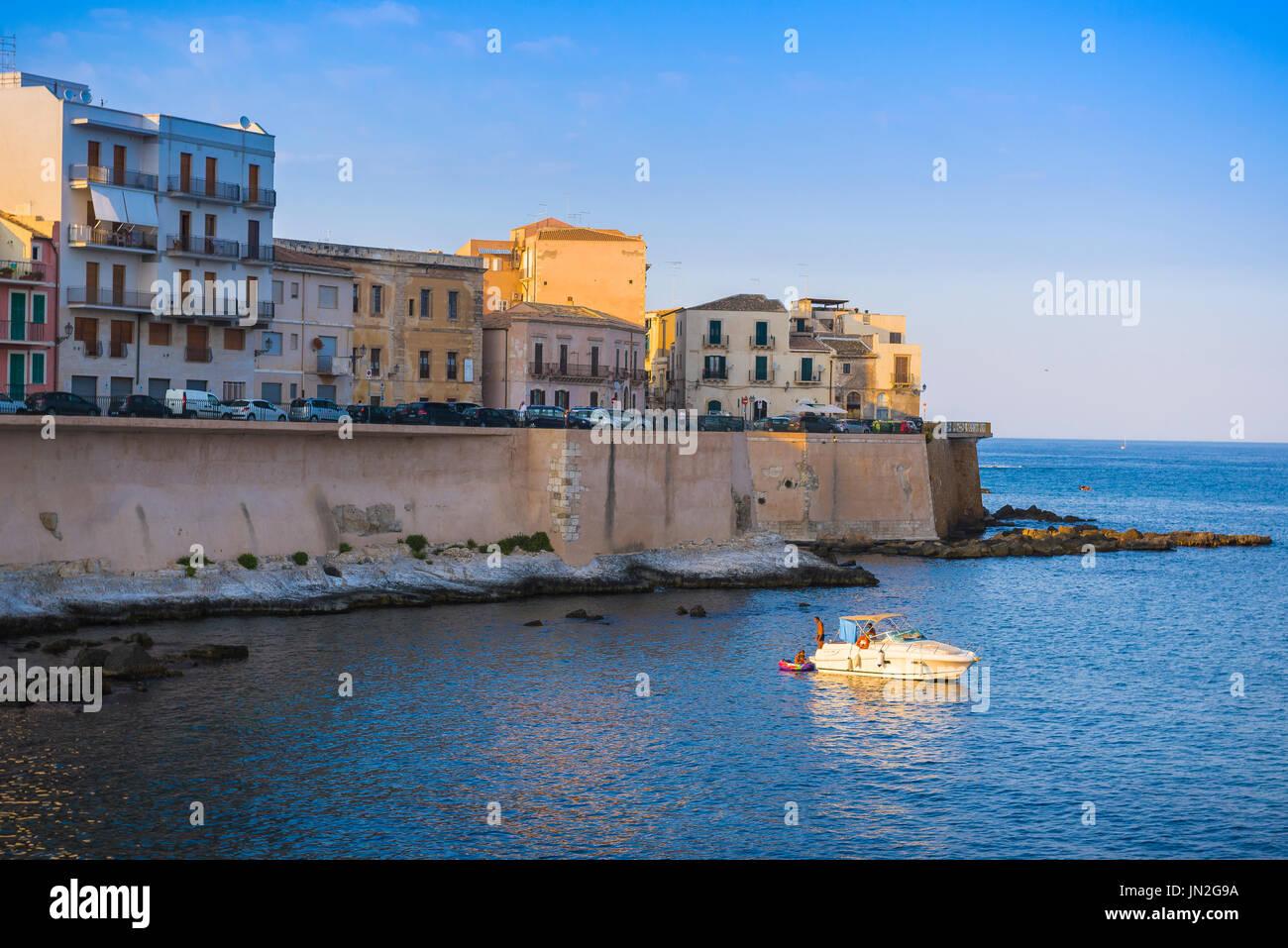 Sicilia bay, al tramonto in una piccola baia a sud dell isola di Ortigia (Siracusa) Sicilia, una famiglia potrete rilassarvi su una barca di svago. Immagini Stock