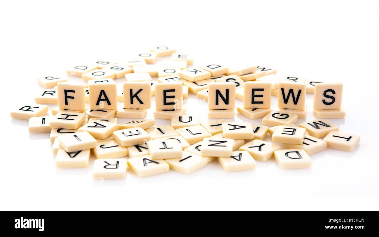 Fake News esplicitate su piastrelle di parola su uno sfondo bianco. Immagini Stock