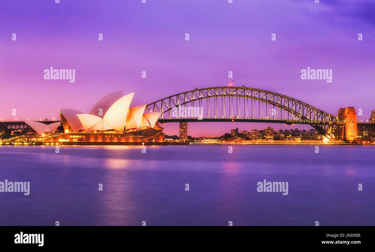 Sydney, Australia - 11 Luglio 2015: Sydney Opera House e Harbour Bridge al tramonto contro magenta colorati sky e sfocata riflettendo acque di Sydne Immagini Stock