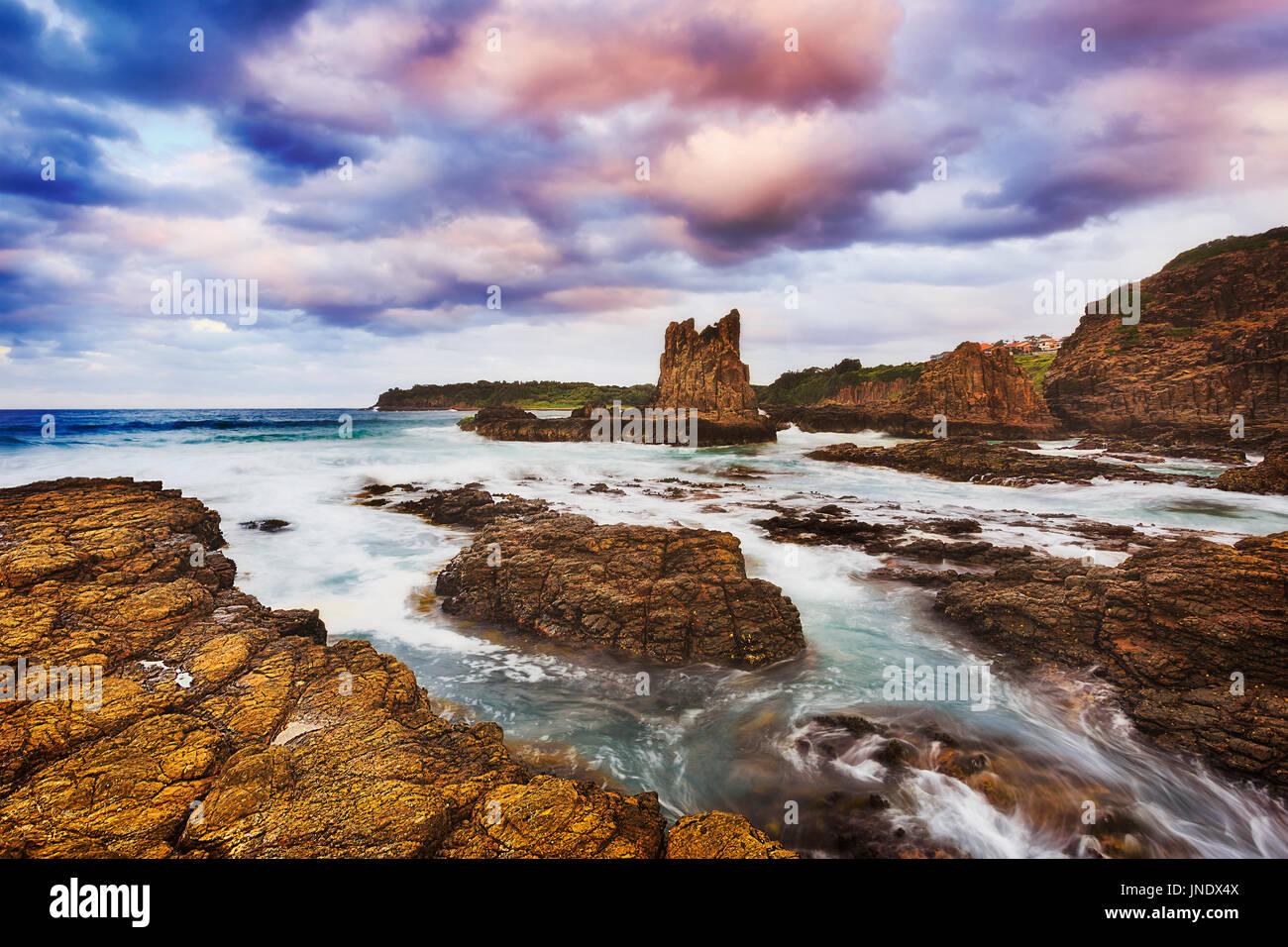 Robusto costa rocciosa intorno bombo beach in Kiama città su Australian Pacific shore. Sfocata flussi di surf a terra erodendo scogliere di arenaria e cattedrale boul Immagini Stock