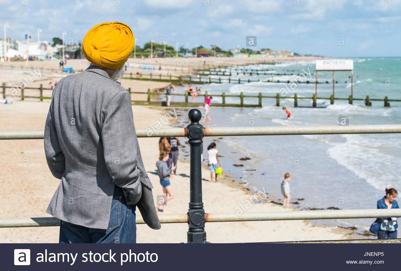 La religione sikh testa di uomo con turbante in piedi su un molo guardando una spiaggia e mare in estate a Littlehampton, West Sussex, in Inghilterra, Regno Unito. Immagini Stock