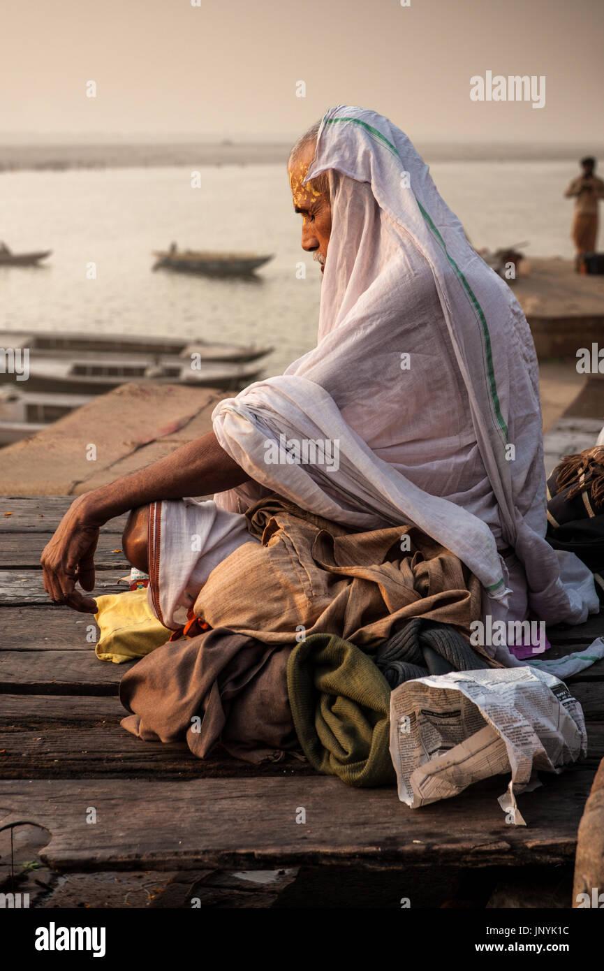 Un pellegrino si siede in alba meditazione del Gange a Varanasi Immagini Stock