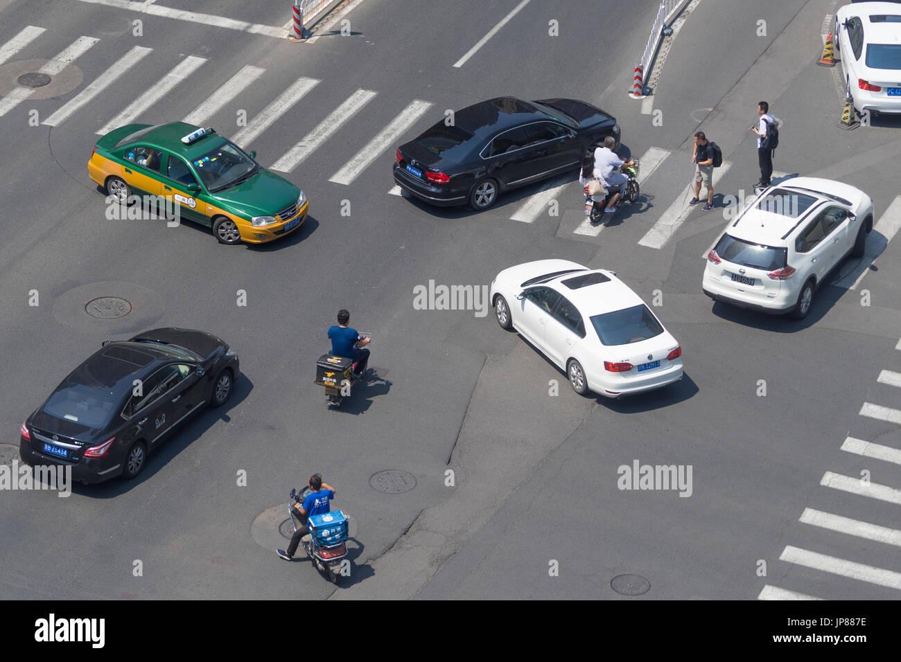 Tipico di Pechino caotico traffico della strada con vetture, ciclomotori e pedoni tutte convergenti su ampi boulevard intersezione Immagini Stock