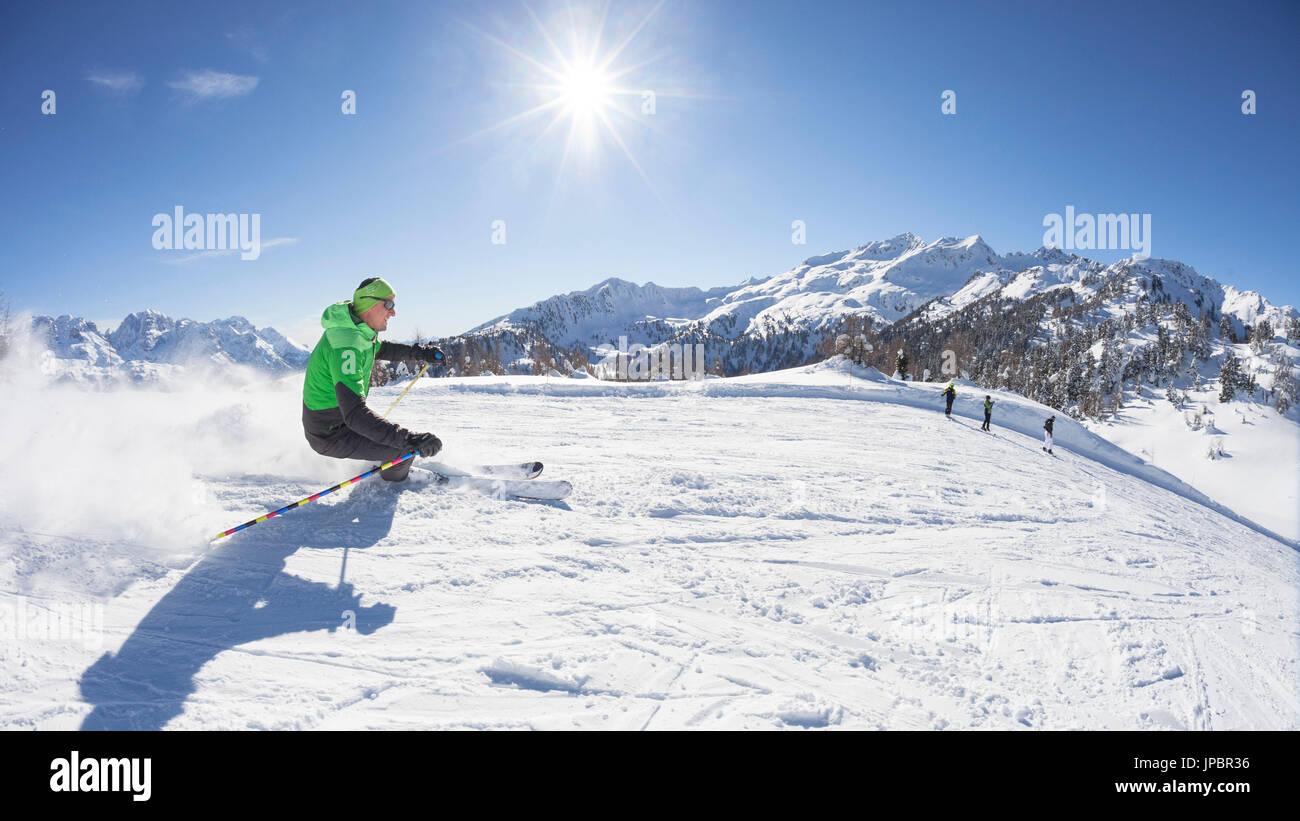 Uno sciatore è lo sci lungo le piste da sci di Folgarida ski resort con Gruppo di Brenta in background, provincia di Trento, Trentino Alto Adige, Italia, Europa Immagini Stock