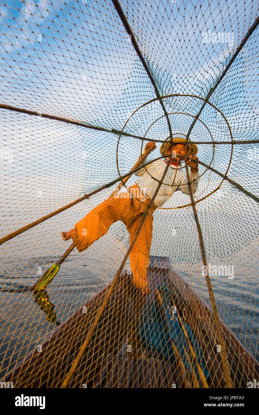 Lago Inle, Nyaungshwe, stato Shan, Myanmar. Fisherman guardando attraverso la rete da pesca. Immagini Stock