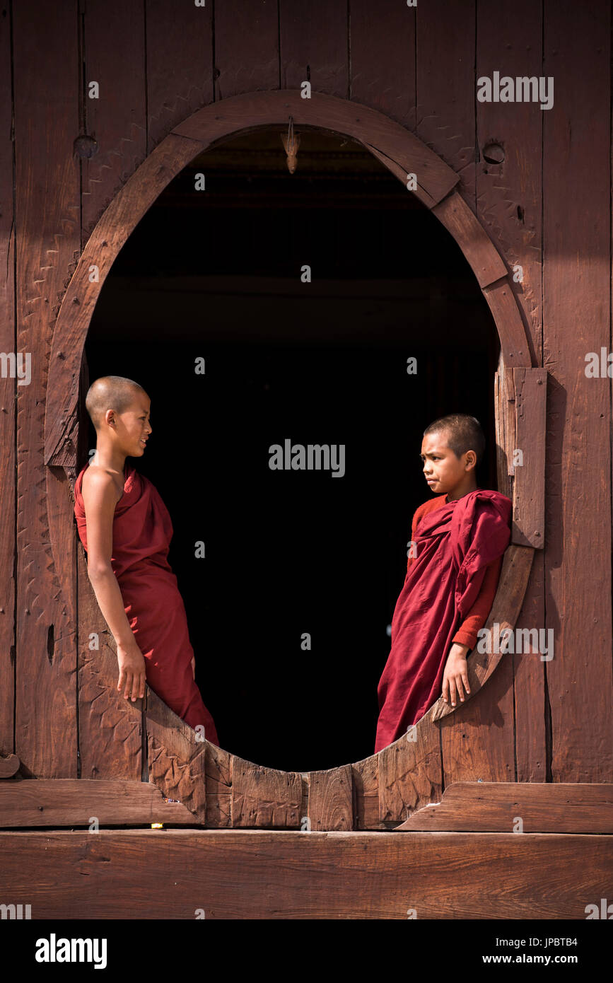 Nyaungshwe, Lago Inle, Stato Shan, Myanmar. Il debuttante monaci a Shwe Yaunghwe Kyaung dalle finestre dell'ordinazione di teak hall Immagini Stock