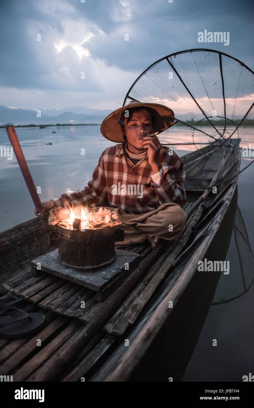 Lago Inle, Nyaungshwe township, Taunggyi distretto, Myanmar (Birmania). Pescatore locale prima dell'Alba con camino sulla barca. Immagini Stock