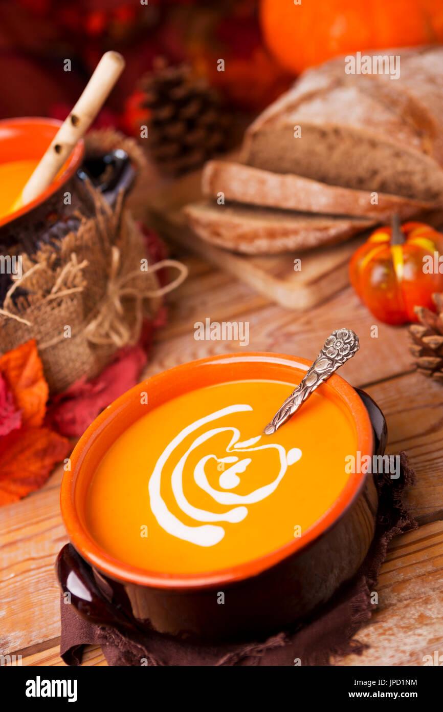 Una ciotola di in casa cremosa zuppa di zucca su un tavolo rustico con decorazioni d'autunno. Immagini Stock