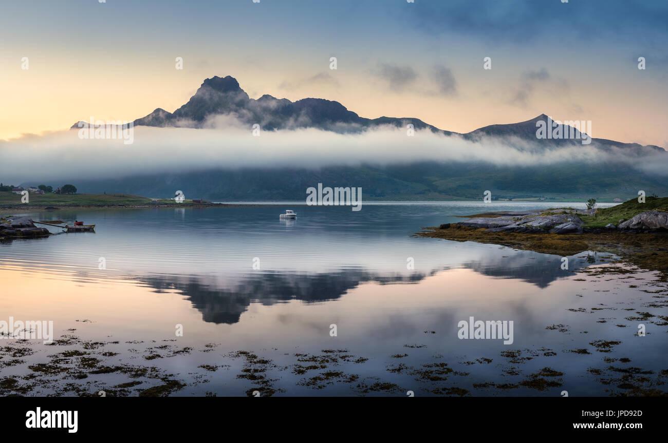 Paesaggio panoramico con la riflessione di montagna e nuvole basse a notte estiva in Lofoten, Norvegia Immagini Stock