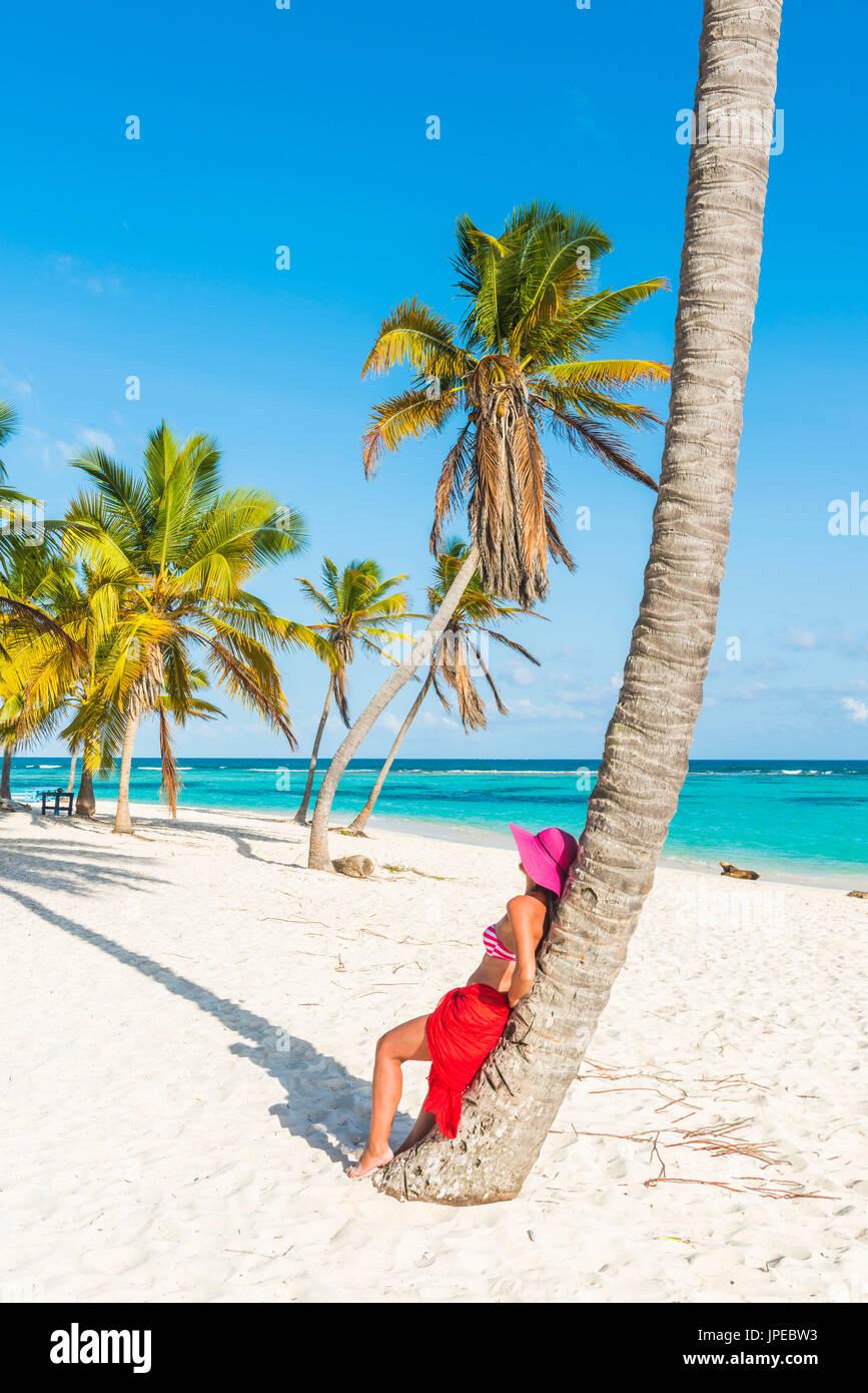 Canto de la Playa, Saona Island, Parco Nazionale Orientale (Parque Nacional del Este), Repubblica Dominicana, Mar dei Caraibi. Bella donna con red sarong rilassante sulla spiaggia orlata di palme (MR). Immagini Stock